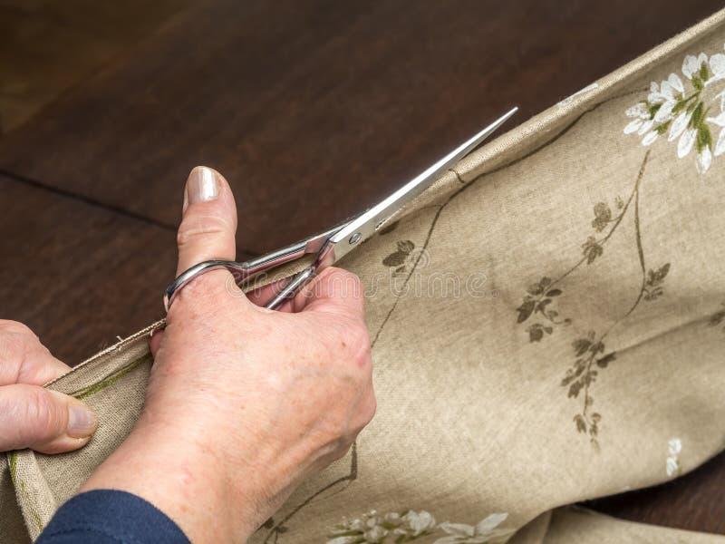 Alteration. Closeup of senior woman's hands cutting linen in half using scissors stock image