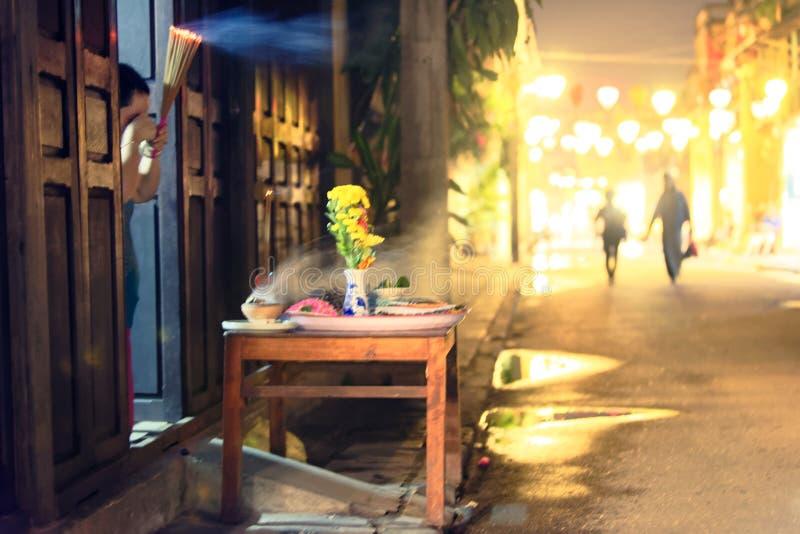 Altere y los peatones en las calles de Hoi An, Vietnam en la noche imagenes de archivo