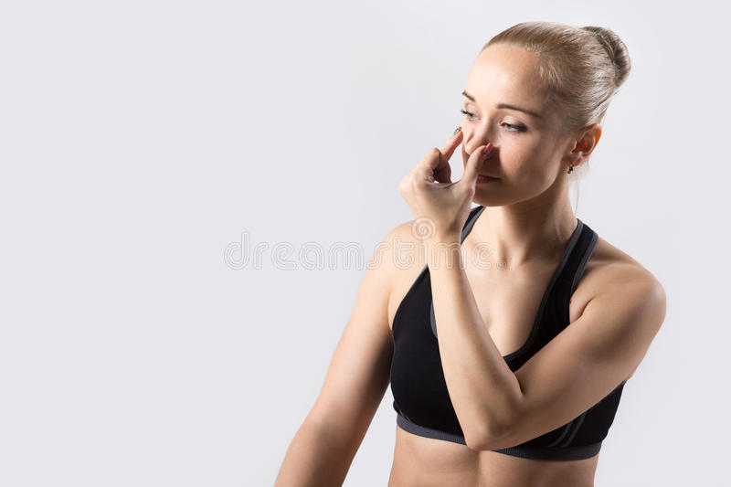 Alternate Nostril Breathing. Portrait of sporty beautiful young woman practicing yoga, nadi shodhana pranayama (Alternate Nostril Breathing), copy space, studio royalty free stock photography
