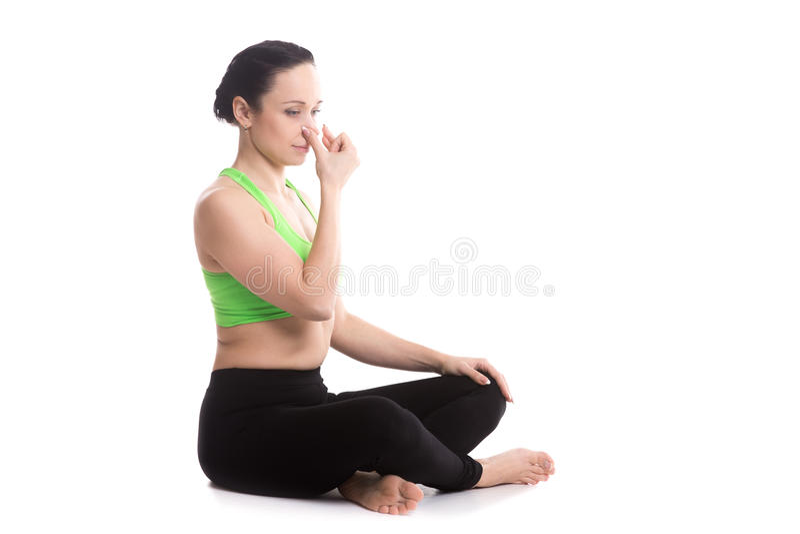 Alternate Nostril Breathing in yoga Sukhasana pose. Calm beautiful girl practicing hatha yoga nadi shodhana pranayama (Alternate Nostril Breathing), sitting stock images