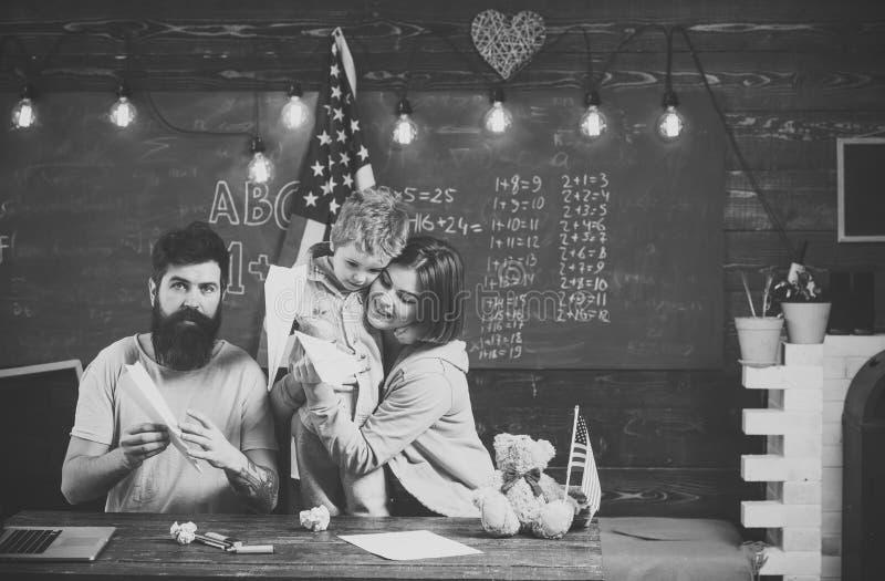 Alternatief onderwijs Homeschoolingsconcept Ouders die zoon het Amerikaanse tradities spelen onderwijzen Amerikaanse familie bij  stock foto's