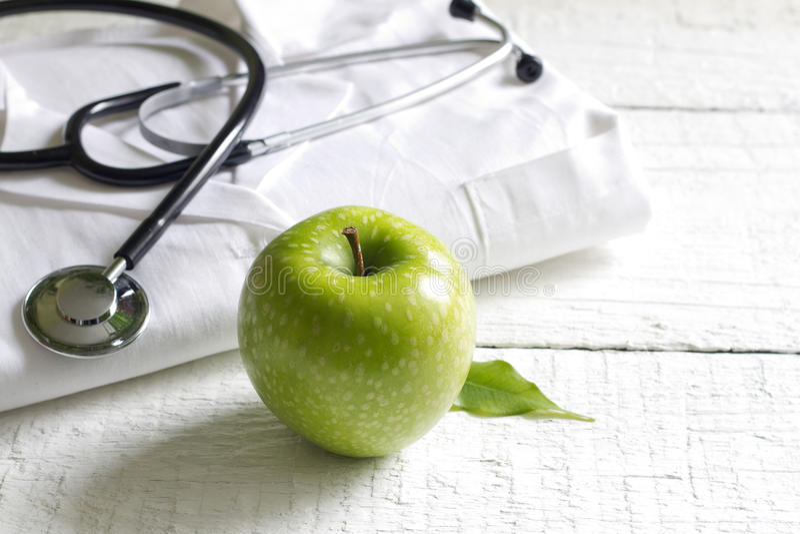Alternatieve geneeskundestethoscoop en groene symboolachtergrond royalty-vrije stock afbeeldingen