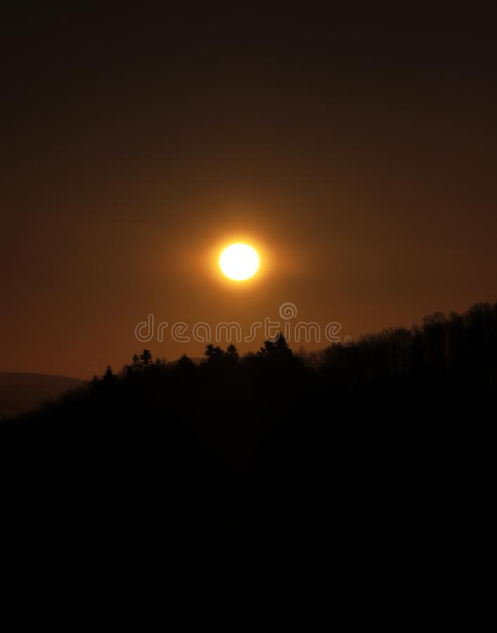 Alternating with black, grey and orange blaze. Wonderful yellow and orange ball with shining to surroundings. Huge energy in one. Small ball on the sky stock images