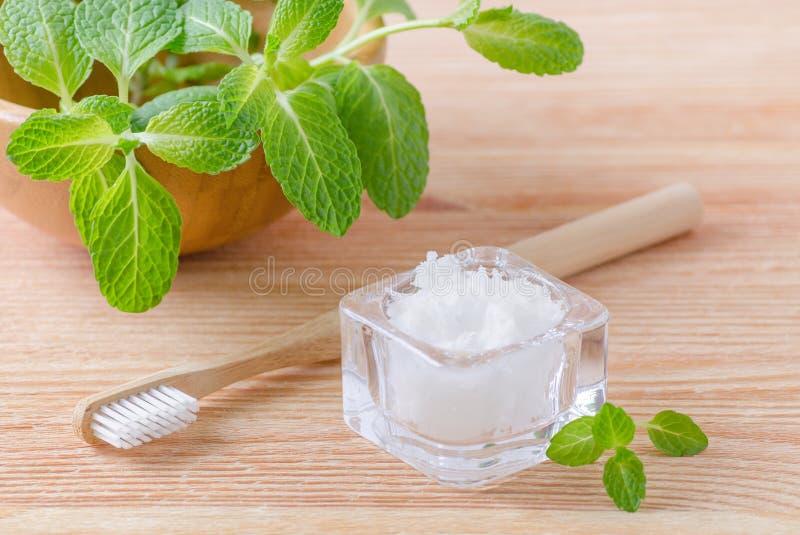 Alternativ naturlig tandkrämkokosnötolja och trätandborstecloseup, mintkaramell på trä royaltyfri bild