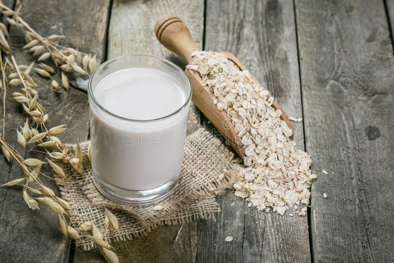 Alternativa de la leche de la avena en fondo de madera rústico foto de archivo