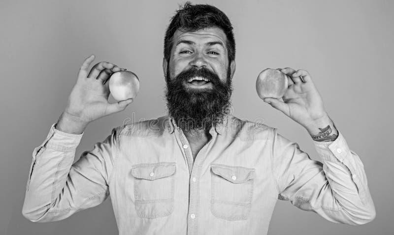 Alternativa sana Sirva las manzanas sonrientes barbudas de los controles en fondo del azul de las manos Concepto totalmente sano  fotos de archivo