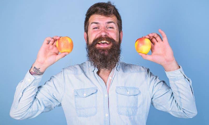 Alternativa sana Sirva las manzanas sonrientes barbudas de los controles en fondo del azul de las manos Concepto totalmente sano  fotos de archivo libres de regalías