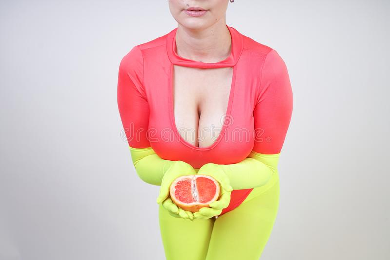 Alternative caucasian girl with short hair dressed in sporty red spandex bodysuit and bright tights with green neon gloves. curvac royalty free stock photos
