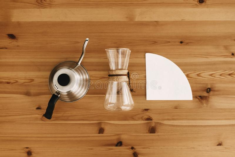 Alternative coffee brewing method, flat lay. Stylish accessories and items for alternative coffee on wooden table. Steel kettle, stock photos