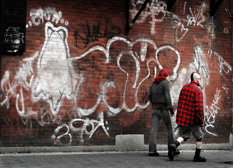 Alternative culture. Young couple against the graffiti wall