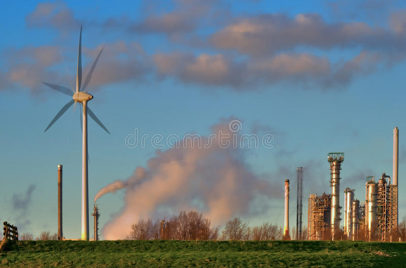 Emission. Global warming concept with alternative energy of windmills in contrast to the emission of a refinery plant stock image