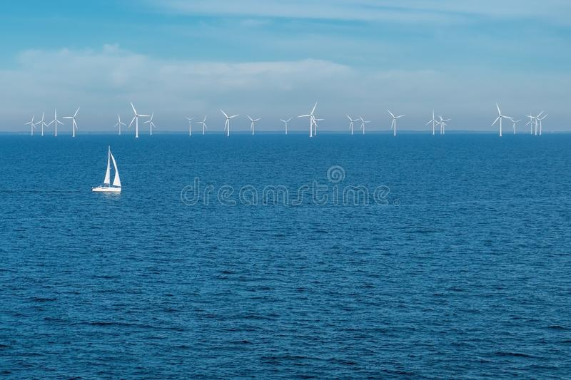 Alternative energy - row of offshore wind turbines and yacht at sea, green energy windmill generators at sea stock photography