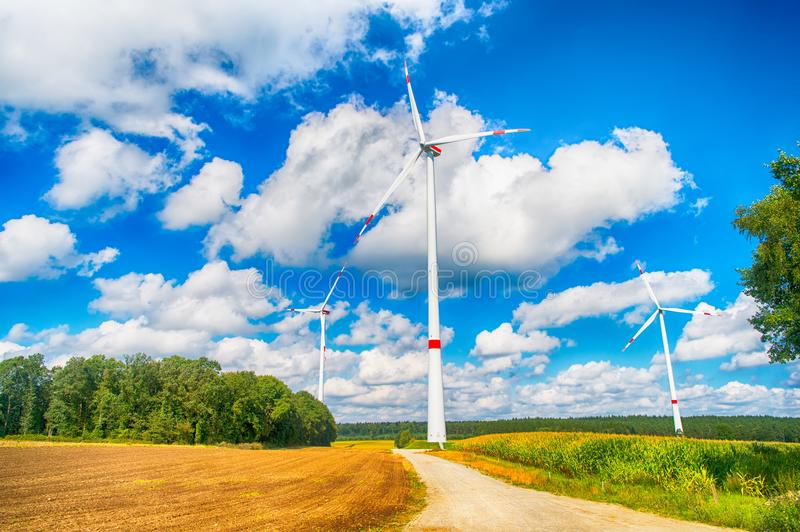 Alternative energy source. Turbines on field on cloudy blue sky. Wind farm in Lower Saxony, Germany. Global warming, climate change. Eco power, green stock photography
