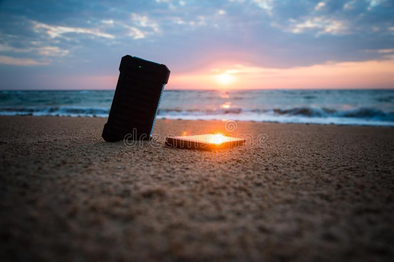 Alternative energy source. Powerbank in the sand on the background of the rising sun in the cloudy sky and blue sea. Alternative energy source. battery is stock photography