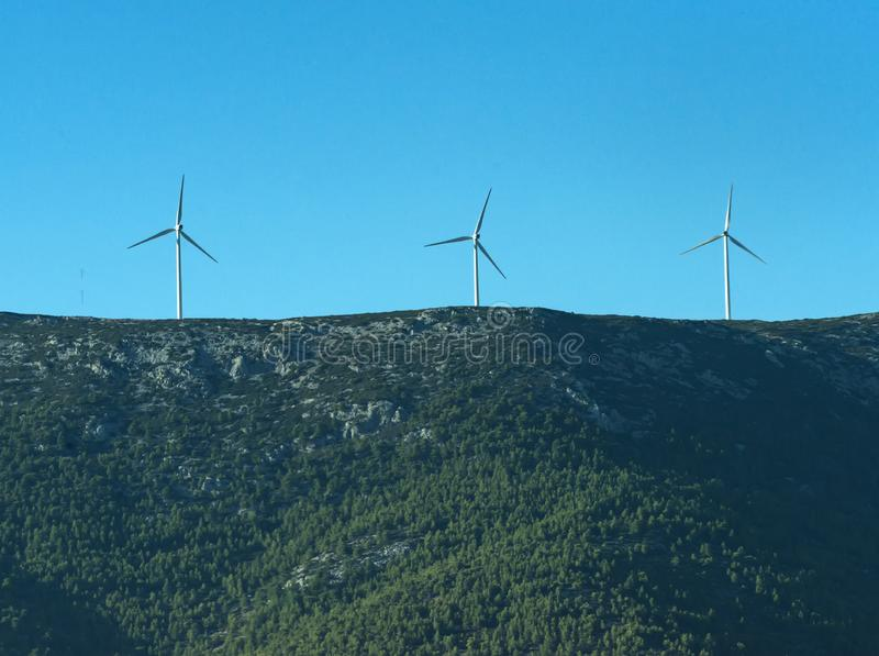 Alternative energy sources concept. Giant white windmills on mountains. Windmills, wind generators on hill, mountain. Landscape with mountains, green forest on stock photo