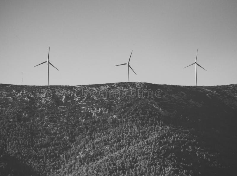 Alternative energy sources concept. Giant white windmills on mountains. Windmills, wind generators on hill, mountain. Landscape with mountains, green forest on royalty free stock images