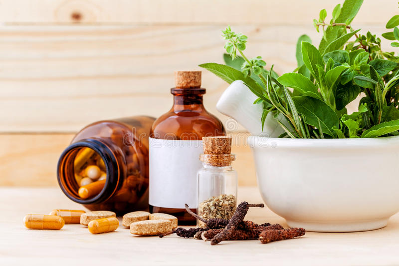 Alternative health care fresh herbal ,dry and herbal capsule wi. Th mortar on wooden background royalty free stock images