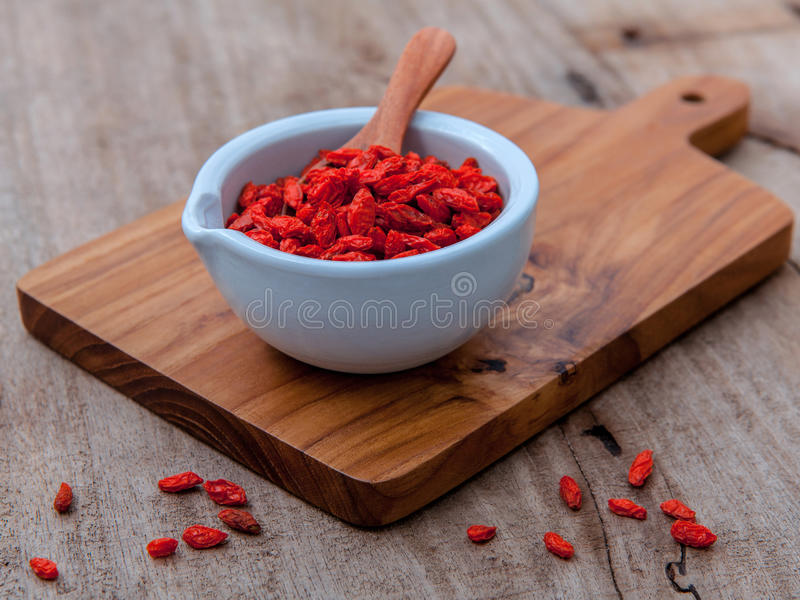 Alternative health care and oriental food ingredients dried Tibetan goji berries on old wooden background. stock images