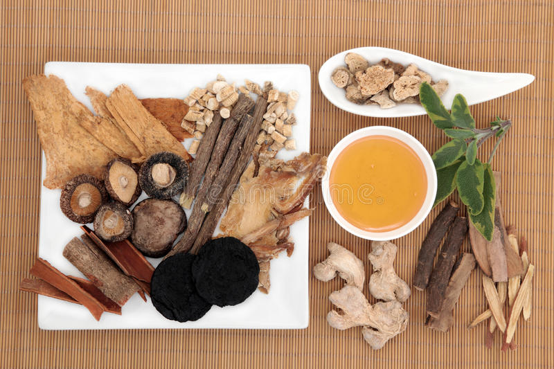 Alternative Healthcare. Traditional chinese herbal medicine selection with honey over bamboo royalty free stock photos