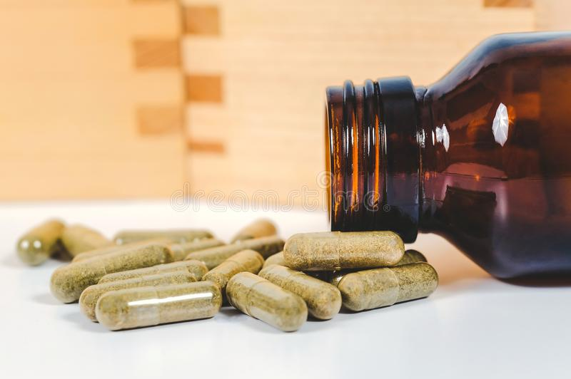 Alternative herb capsule spill out of bottle ,health. Concept stock photography