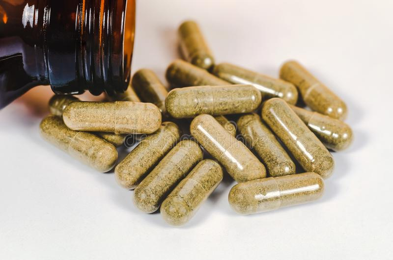 Alternative herb capsule spill out of bottle ,health. Concept royalty free stock photography
