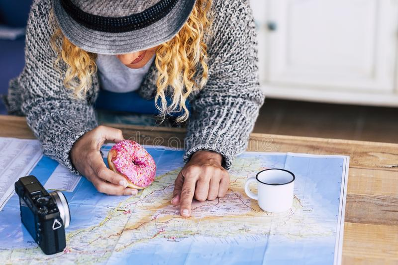 Alternative hipster travel young girl planning her next adventure trip on a island - paper old map on a wooden table and vintage stock image