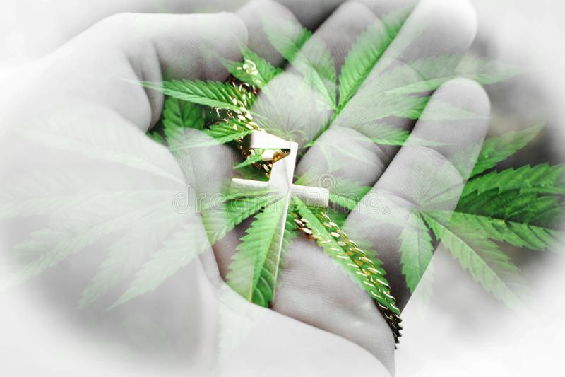Alternative Kräutermedizin-Art With Gold Cross In-Palme der Hand mit Hanf verlässt hohe Qualität lizenzfreie stockfotografie