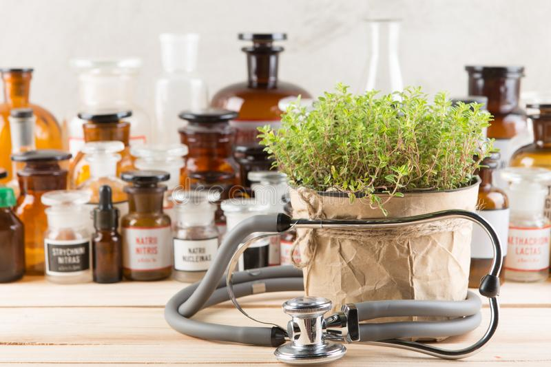 Alternative medicine concept medicine in bottles, medicinal herbs and stethoscope on a wooden table stock images