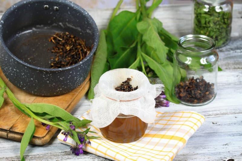 Alternative medicine, filtering comfrey ointment royalty free stock photos