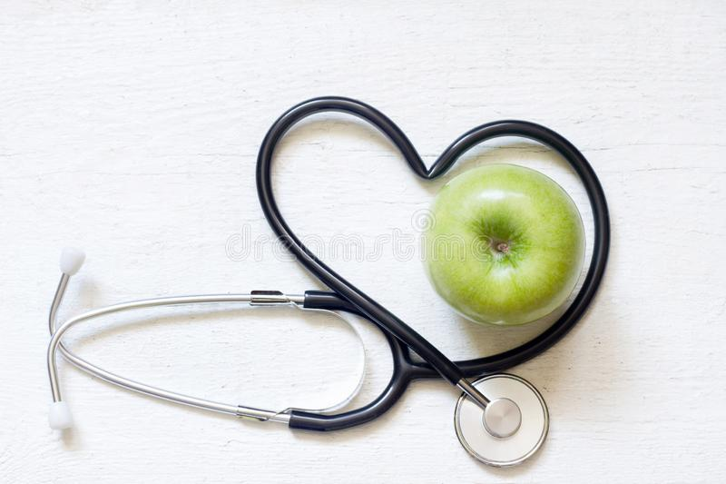 Alternative medicine healthy sign concept with stethoscope heart and green apple on white background stock photo