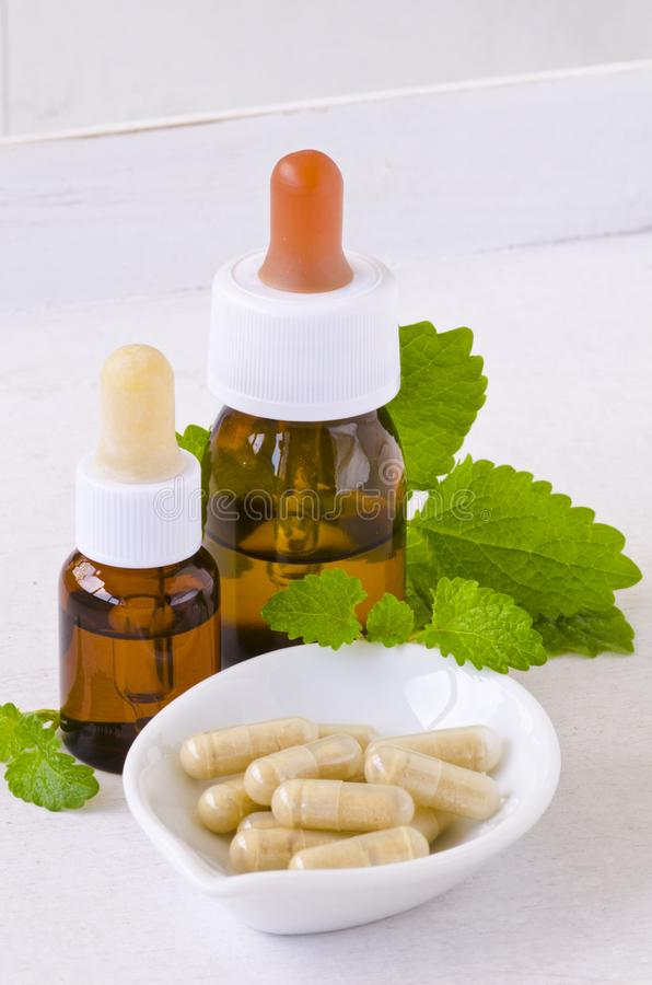 Alternative Medicine. Melissa capsules and essential oil. stock photography