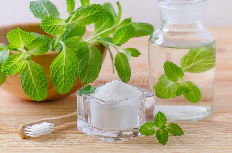 Alternative natürliche Mundwasserflasche mit Zahnpastaxylitol, Soda, Salz und hölzerner Zahnbürstennahaufnahme, Minze auf hölzern stockfotografie