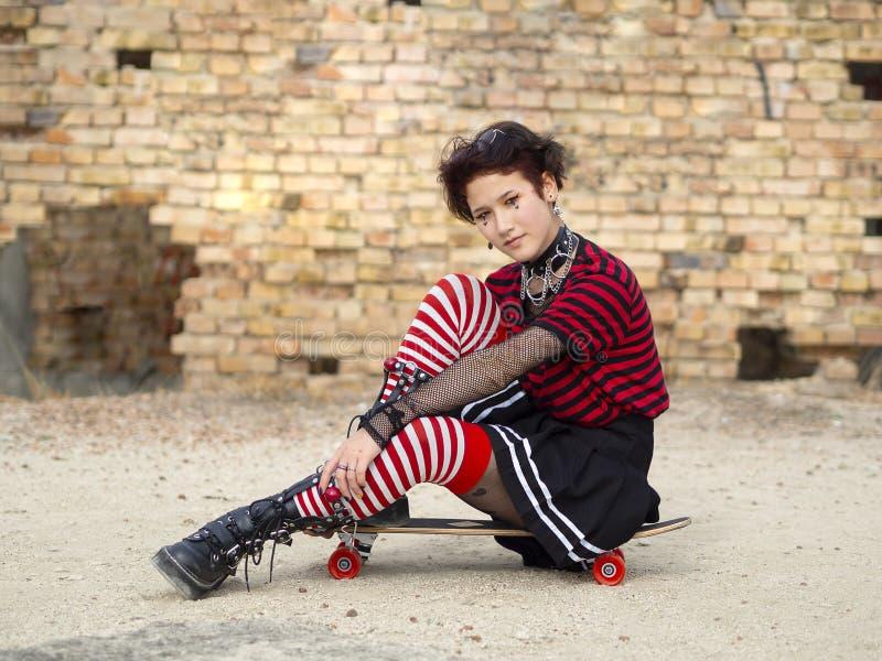 Alternative punk girl sitting on a skate board on a brick wall background. Goth dark teen concept stock image