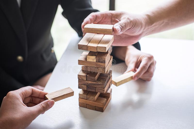 Alternative Risk and Strategy in Business, Hand of business team cooperative gambling placing making wooden block hierarchy on the stock photography