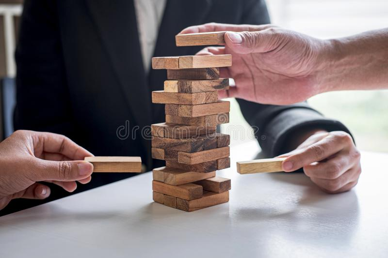 Alternative Risk and Strategy in Business, Hand of business team cooperative gambling placing making wooden block hierarchy on the royalty free stock image