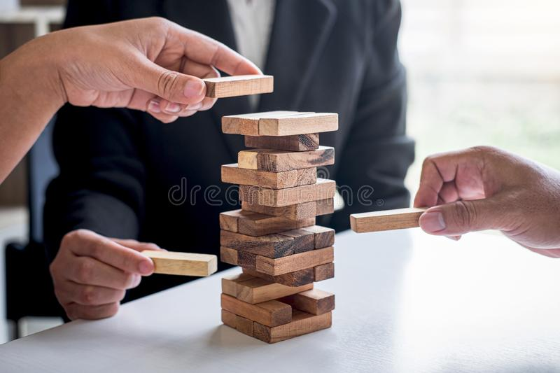 Alternative Risk and Strategy in Business, Hand of business team cooperative gambling placing making wooden block hierarchy on the royalty free stock photos