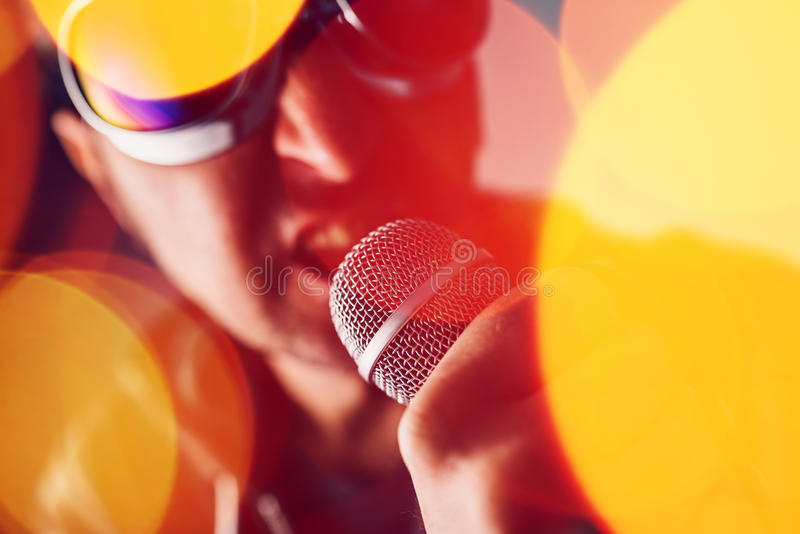Alternative rock music singer singing song into microphone. Bokeh light effect and selective focus royalty free stock photography