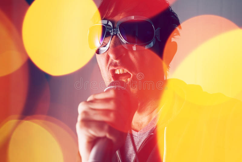 Alternative rock music singer singing song into microphone. Bokeh light effect and selective focus stock photos