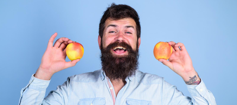 Alternative saine Le sourire barbu d'homme tient des pommes à l'arrière-plan de bleu de mains Nutrition suivante un régime de vit photo libre de droits