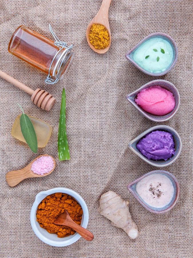 Alternative skin care and homemade scrubs with natural ingredients sage ,turmeric ,sea salt ,honey, aloe. Vera,lemon ,rosemary,mint and sesame set up on brown royalty free stock image