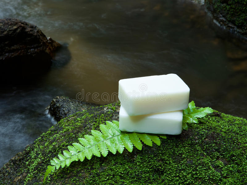 Alternative skin care homemade soap on stone, green leaf with tr. Opical waterfall in the background. as a spa concept stock photography