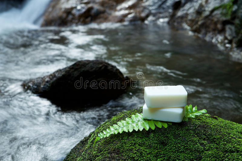 Alternative skin care homemade soap on stone, green leaf with tr. Opical waterfall in the background. as a spa concept stock images