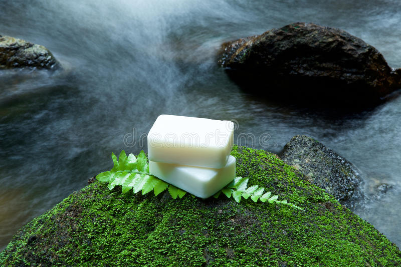 Alternative skin care homemade soap on stone, green leaf with tr. Opical waterfall in the background. as a spa concept stock image