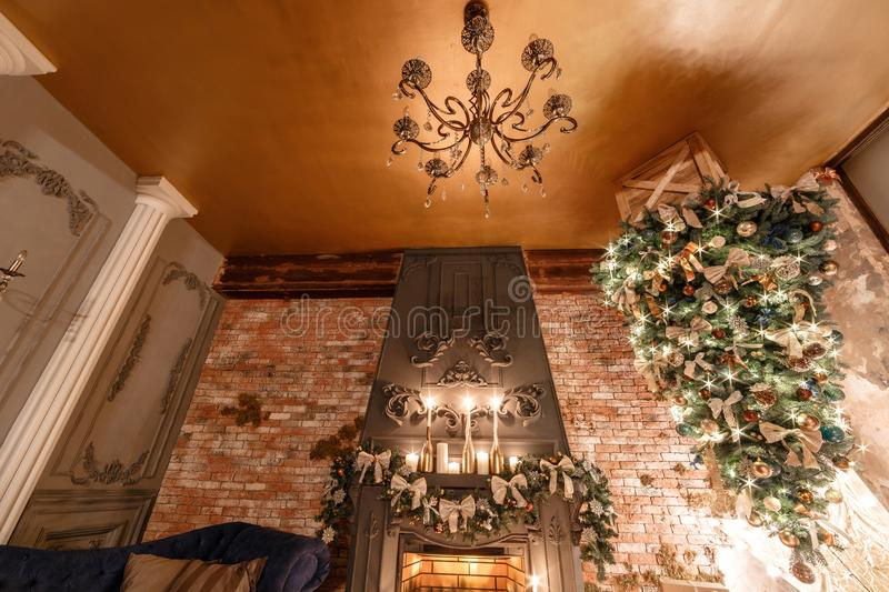 Alternative tree upside down on the ceiling. Winter home decor. Modern loft interior with fireplace and brick wall.  royalty free stock photos