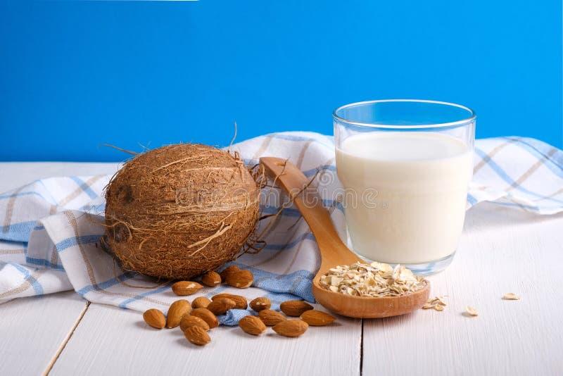 Alternative types of milks. Vegan substitute dairy milk. Glass of milk, coconut, almond nuts, oat flakes on wooden table on blue stock photos