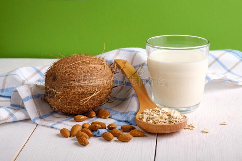 Alternative types of milks. Vegan substitute dairy milk. Glass of milk, coconut, almond nuts, oat flakes on wooden table on green royalty free stock images