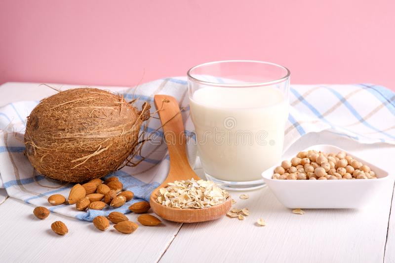 Alternative types of milks. Vegan substitute dairy milk. Milk glass, coconut, almond nuts, soy, oat flakes on wooden table on pink royalty free stock photography