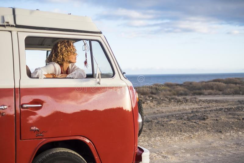 Beautiful young woman caucasian in leisure activity with a old van in vacation stock photo