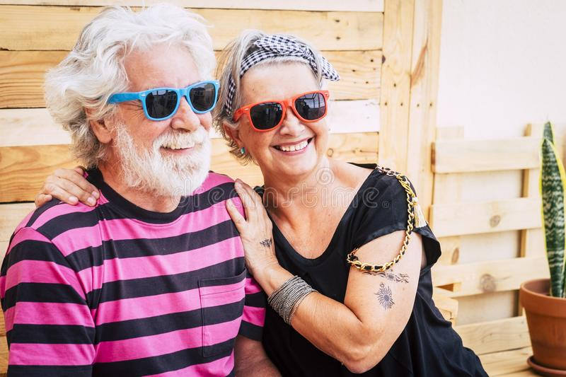 Alternative youthful senior old couple with white hair enjoying together hugging and smiling in outdoor leisure activity - trendy. And coloured look for no royalty free stock photos