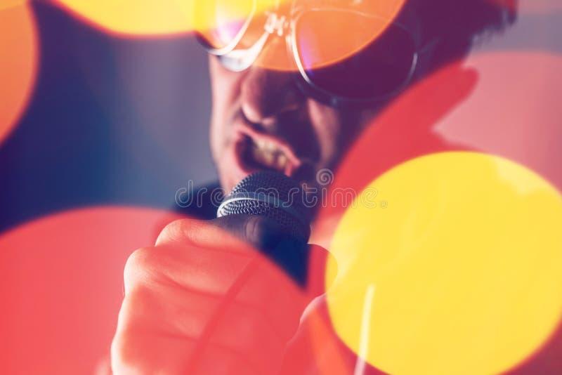 Alternativet vaggar sjungande sång för musiksångare in i mikrofonen royaltyfri bild
